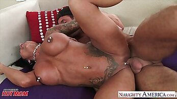 Alluring tattooed brunette mother wanks her throbbing cock while on the phone